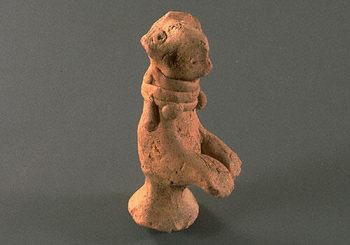 Figurine of begging dog with upraised front paws and wearing a beaded collar. The back legs have been shaped into a stand. Hand formed with applique ornaments and eyes.