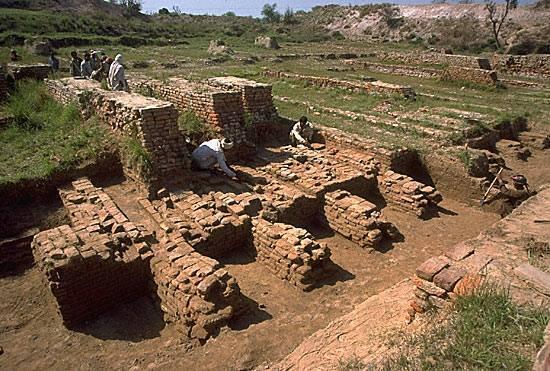 "After clearing the overlying silt, the original forms of the baked brick walls and hollow buttresses of the ""granary"" could be made out. The three high walls in the upper left of the image are part of a later rebuilding of the entire structure after ca. 2200 BC."