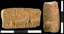 Molded terra cotta tablet (H2001-5075/2922-01) with a narrative scene of a man in a tree with a tiger looking back over its shoulder. The tablet, found in the Trench 54 area on the west side of Mound E, is broken, but was made with the same mold as ones found on the eastern side of Mound E and also in other parts of the site (see Indus Slides 89 for right hand portion of same scene). The reverse of the same molded terra cotta tablet shows a deity grappling with two tigers and standing above an elephant.