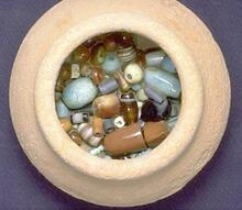 Initial probing to determine the contents of this small pot (169) from Trench 38, Late Harappan Period, revealed the presence of carnelian and faience beads. After removal of the overlying sediment it was clear that the pot was filled with beads. Each bead was mapped in and then photographed before removal. In the lower levels were many tiny beads that had settled to the bottom.