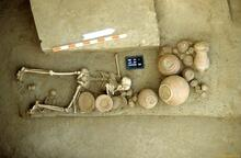 His burial was disturbed in antiquity, possibly by ancient Harappan grave robbers. Besides the fact that the body is flipped and the pottery disturbed, the left arm of the woman is broken and shell bangles that would normally be found on the left arm are missing. The infant was buried in a small pit beneath the legs of the mother.
