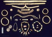This collection of gold and agate ornaments includes objects found at both Mohenjo-daro and Harappa. At the top are fillets of hammered gold that would have been worn around the forehead.  The other ornaments include bangles, chokers, long pendant necklaces, rings, earrings, conical hair ornaments, and broaches. Such ornaments were never buried with the dead, but were passed on from one generation to the next. These ornaments were hidden under the floors in the homes of wealthy merchants or goldsmiths.